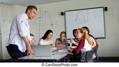 Animation of mathematical equations floating over schoolchildren and teacher using laptop computer and talking. Education back to school concept digitally generated image.