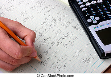 Student's writing-book with mathematical formulas, the calculator and a hand of the student with a pencil.