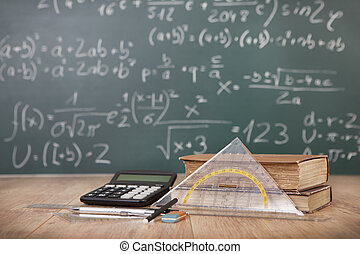 Mathematical lesson - Schoolbooks and calculator lying on a...
