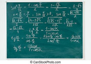 Maths formulas written by white chalk on the blackboard.