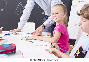Shot of a little girl smiling at the camera during a math lesson