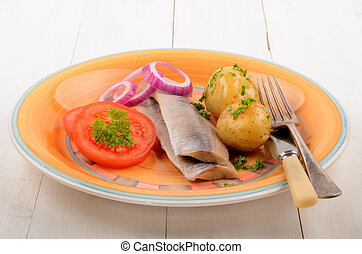 matjes herring and boiled potatoes with tomato on a plate