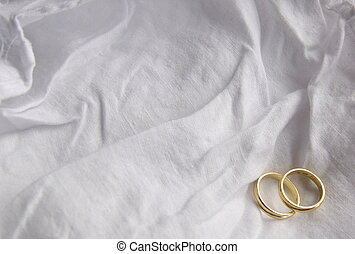 two wedding rings in the corner of a white cloth background