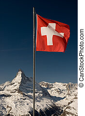 A mountaintop view of the national flag of Switzerland with the Matterhorn in the background.
