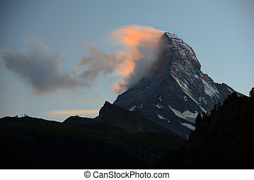 Matterhorn in early morning with alpenglow and cloud on peak...