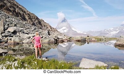 Tourist woman in meditation at Riffelsee Lake with Matterhorn reflected in its calm waters. Tourism in Zermatt, Swiss Alps, Valais, Switzerland. Riffelsee is located on Gornergrat Bahn cog railway.