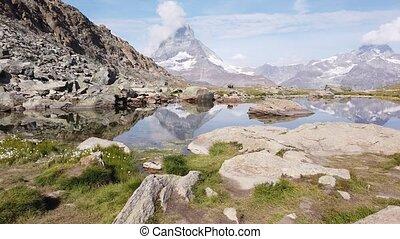 Matterhorn on Riffelsee Lake - Alpine meadows around ...