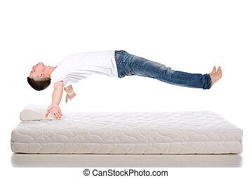 Mattress - Orthopedic mattress. A young man sleeping on a...