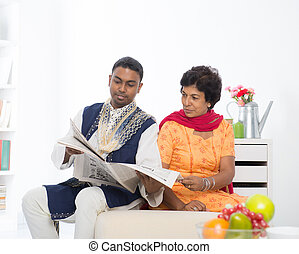Mature 50s Indian woman reading a book with her son at home