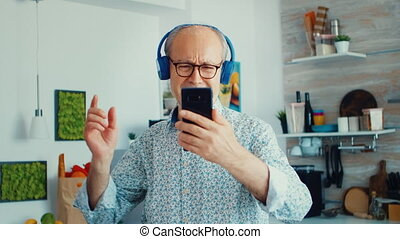 Happy mature adult listening music wearing headphones in kitchen during breakfast. Elderly retired person enjoying modern fun happy lifestyle, dancing relaxed, smiling and using modern technology