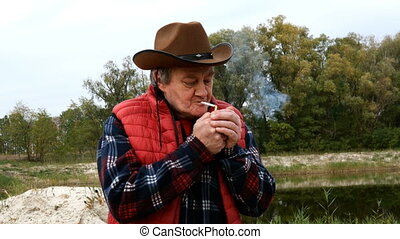 Mature adult man in cowboy hat and clothes, set fire cigarette from lighter and inhales smoke with pleasure. In countryside or ranch. Medium shot. Outdoors.
