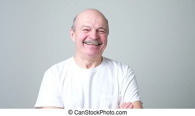 Mature adult man laughing looking at the camera. Positive...