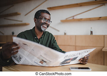 businessman with newspaper in cafe