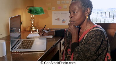 Mature African American small business owner working in her...