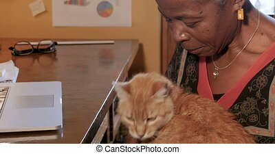 Mature African American woman petting her orange cat in her home office