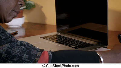 Mature African American woman writing in a notebook next to her laptop