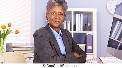 Mature African businesswoman sitting at desk