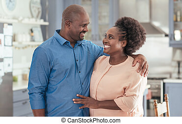 Mature African couple standing affectionately together in their kitchen