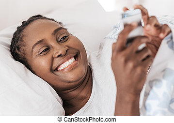 Mature African woman checking her phone while lying in bed -...