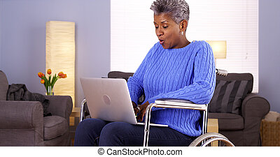 Mature African woman sitting in wheelchair with laptop