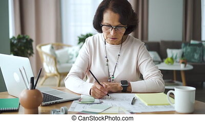 Mature american businesswoman working with design blueprint, watching laptop at desk in home office.