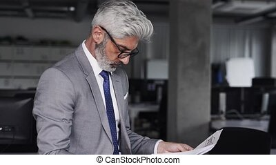 Mature architect in gray suit in the office. - Mature...