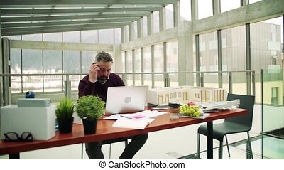 Mature architect with laptop and model of a house in office,...