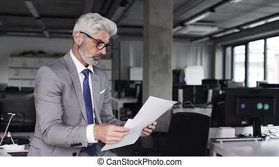 Mature architect with smartphone in the office. - Mature...