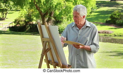Mature artist painting on a canvas in the countryside