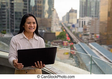Mature Asian businesswoman against view of the city