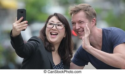 Mature Asian businesswoman and young Scandinavian man using phone together in the streets outdoors