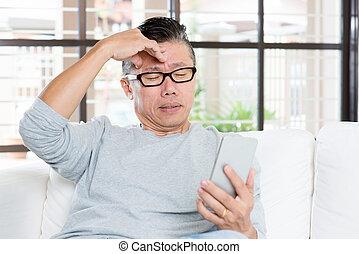 Mature Asian man headache while using smartphone