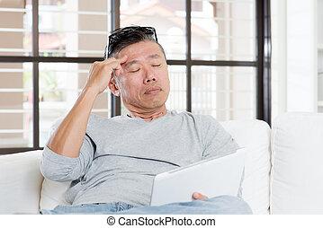 Mature Asian man headache while using tablet computer