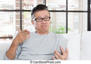 Mature Asian man unhappy while using smartphone