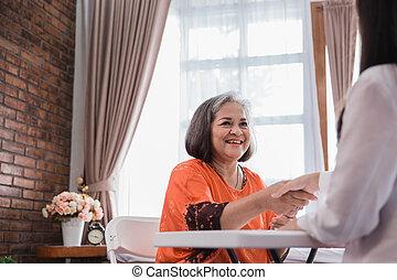 mature asian woman shaking hand