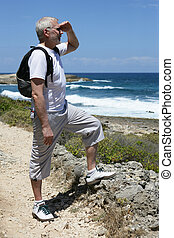Mature backpacker gazing at the ocean