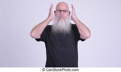 Mature bald bearded man covering ears as three wise monkeys...