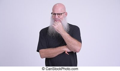 Mature bald bearded man looking serious while thinking -...