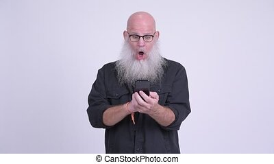 Mature bald bearded man using phone and looking shocked