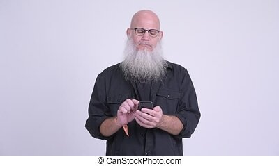 Mature bald bearded man using phone