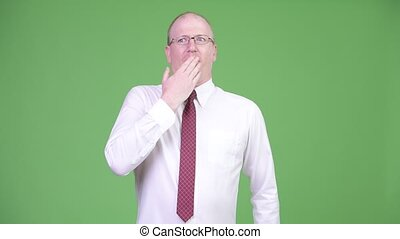 Mature bald businessman covering mouth while looking guilty...