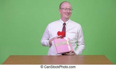 Mature bald businessman flirting at work and looking guilty...