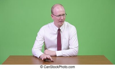 Mature bald businessman looking bored against wooden table -...