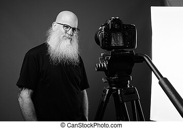 Mature bald man with long beard vlogging in black and white