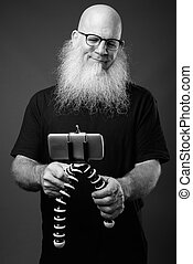 Mature bald man with long beard vlogging with phone