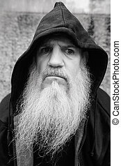 Mature bald man with long gray beard wearing hoodie outdoors