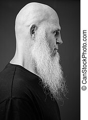 Mature bald man with long white beard in black and white