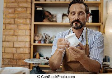 Mature bearded ceramist looking at his handiwork - Looking...