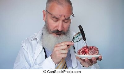 Mature bearded male doctor looking through magnifying glass at heart with knife on plate. Strange doctor concept. Heart surgery concept. Grey background.