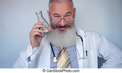 Mature bearded male doctor pours handful of multi-colored ...